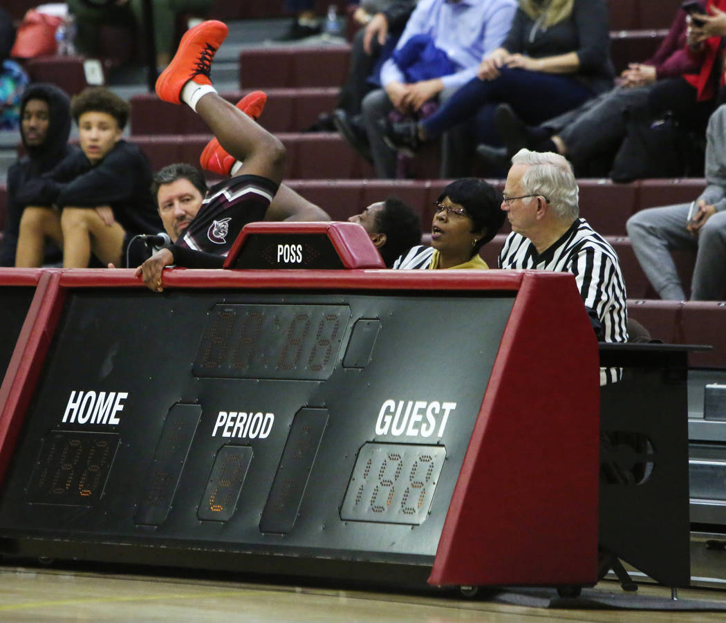 Cimarron Memorial's JaVonte Roberts (14) falls over the official's table during the first half of a basketball game at Faith Lutheran High School in Las Vegas, Tuesday, Jan. 15, 2019. Caroline Bre ...