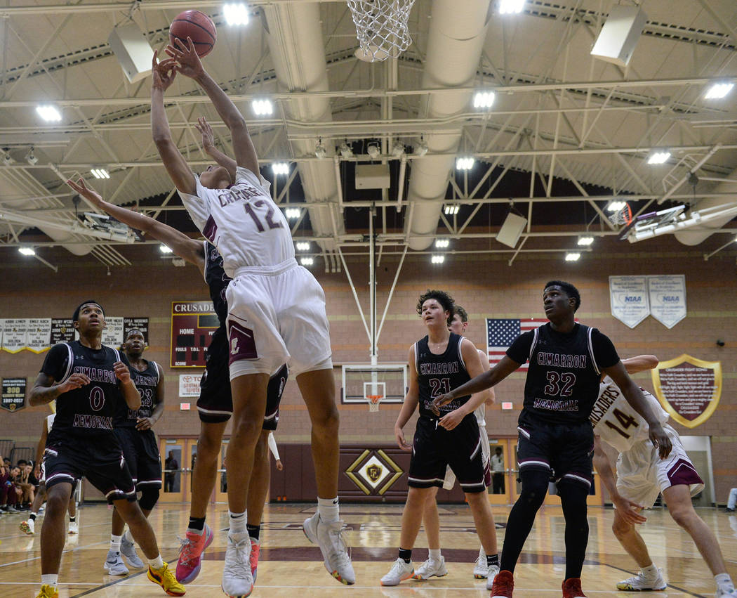 Faith Lutheran's Jackson Williams (12) reaches for the ball while under pressure from Cimarron Memorial's Kevin Johnson (30) during the second half of a basketball game at Faith Lutheran High Scho ...