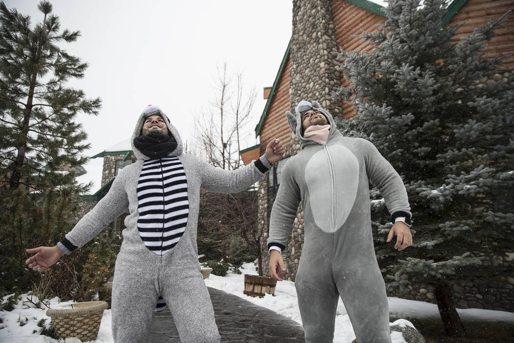 Erick Cano, left, and Yaser Moreno stay warm in their onesies as snow falls outside Mount Charleston Lodge on Tuesday, Jan. 15, 2019, in Las Vegas. Benjamin Hager Las Vegas Review-Journal