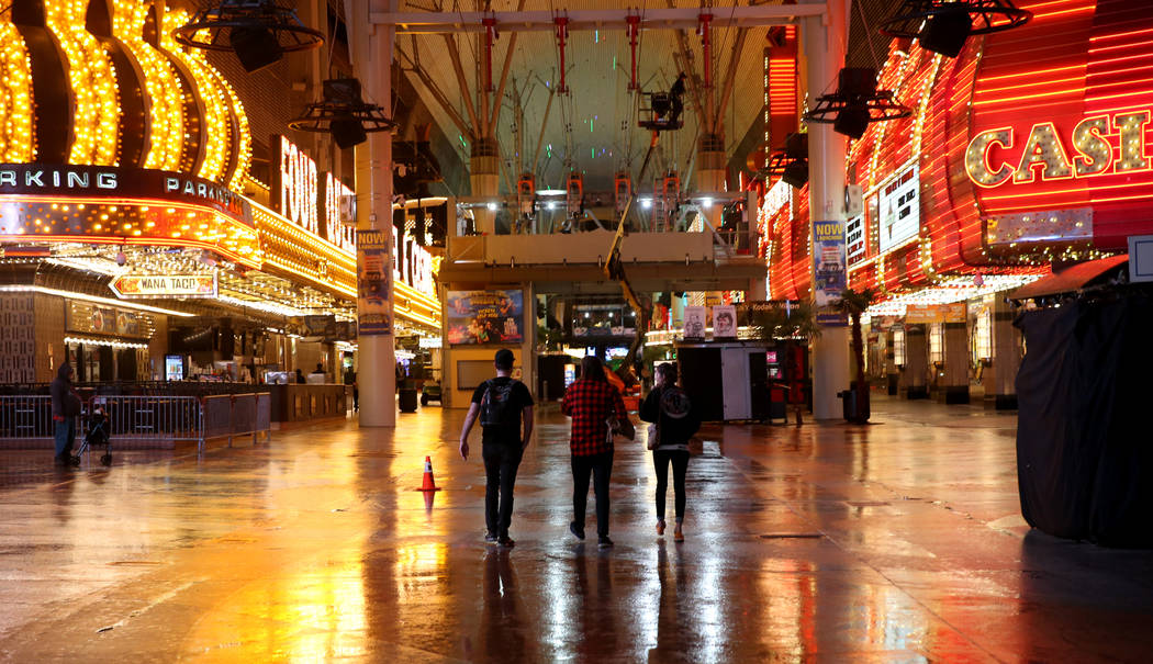 People walk along the Fremont Street Experience after rainfall in downtown Las Vegas, Tuesday, Jan. 15, 2019. (K.M. Cannon/Las Vegas Review-Journal) @KMCannonPhoto