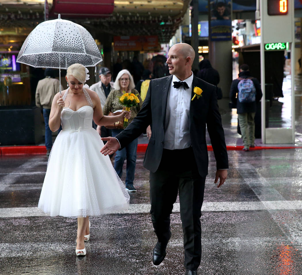 Newly married Kenda and Marcus Fox walk across Casino Center Drive through a light rain in the Fremont Street Experience in downtown Las Vegas Tuesday, Jan. 15, 2019. K.M. Cannon Las Vegas Review- ...