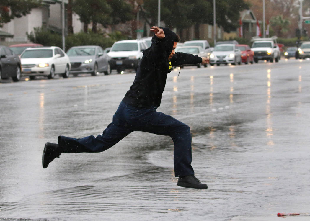 A pedestrian jumps over a flooded street at the intersection of Eastern Avenue and Sahara Avenue on Tuesday, Jan. 15, 2019, in Las Vegas. Bizuayehu Tesfaye/Las Vegas Review-Journal @bizutesfaye