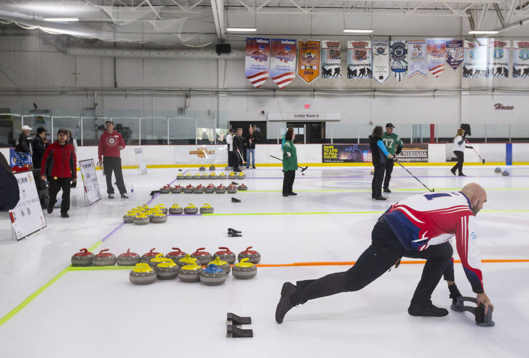 Former NFL player Michael Roos, right, a member of the All Pro Curling Team, warms up before competing in a curling tournament at the Las Vegas Ice Center in Las Vegas on Friday, Jan. 11, 2019. Ch ...