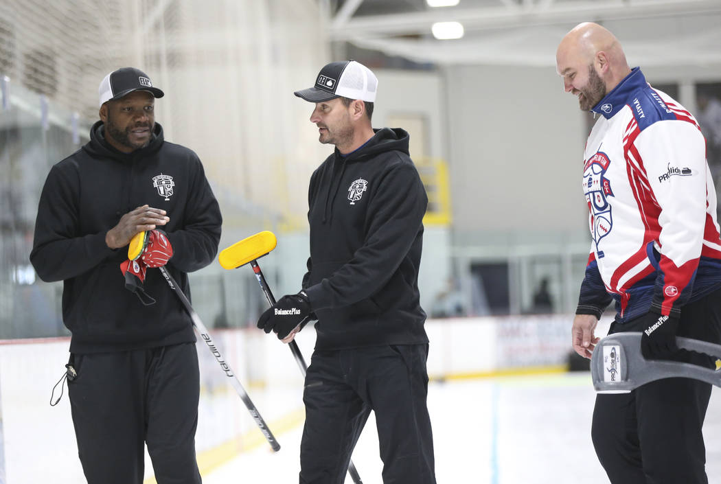 Former NFL players Keith Bulluck, from left, Marc Bulger and Michael Roos, members of the All Pro Curling Team, compete in a curling tournament at the Las Vegas Ice Center in Las Vegas on Friday, ...
