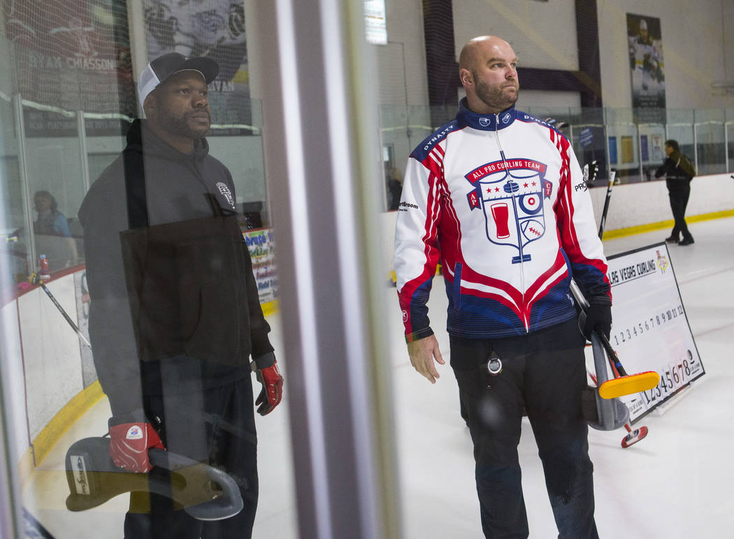 Former NFL players Keith Bulluck, left, and Michael Roos, members of the All Pro Curling Team, look on while warming up for a curling tournament at the Las Vegas Ice Center in Las Vegas on Friday, ...