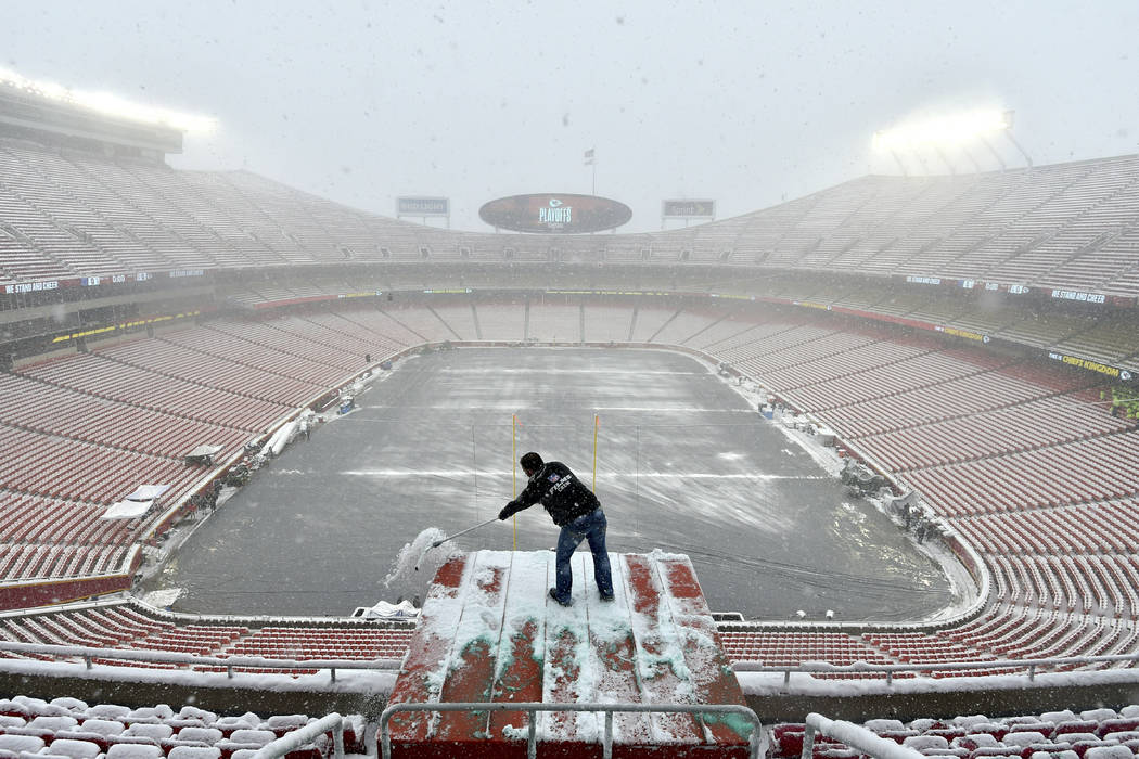 Kyle Haraugh, of NFL Films, clears snow from a camera location at Arrowhead Stadium before an NFL divisional football playoff game between the Kansas City Chiefs and the Indianapolis Colts, in Kan ...