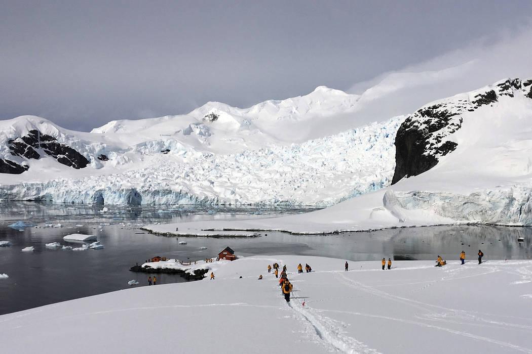 Tourists hike Dec. 7 on an island on the western peninsula of Antarctica. (Wayne Dunn via AP)