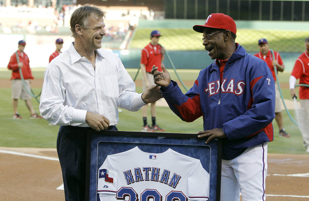 Texas Rangers manager Ron Washington (38), right, greets former Texas Rangers pitcher John Wetteland before the start of a baseball game against the Seattle Mariners at Rangers Ballpark in Arlingt ...