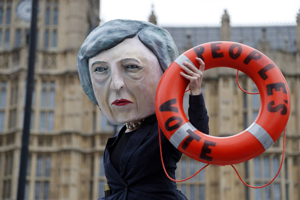 An activist from Avaaz wears a mask of Britain's Prime Minister Theresa May as Pro-European demonstrators protest opposite the Houses of Parliament in London, Tuesday, Jan. 15, 2019. Britain's Pri ...