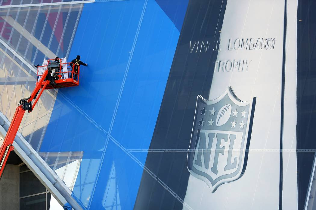 FILE - In this Thursday, Jan. 10, 2019, file photo, workers hang banners on Mercedes-Benz Stadium in preparation for the NFL Super Bowl football game, in Atlanta. Atlanta leaders, police and feder ...