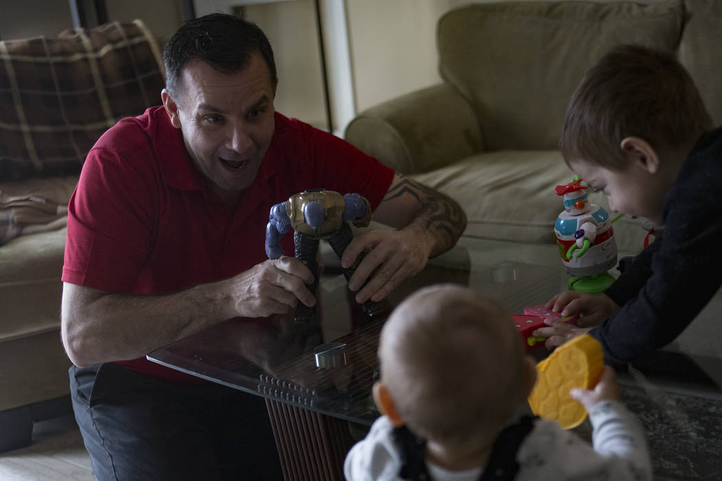 Michael Russell plays with his great nephew Cameron Gonzales, 2, and great niece Ava Gonzales, 11 months, at his home in Las Vegas, Friday, Jan. 11, 2019. When Michael was young, his father died, ...