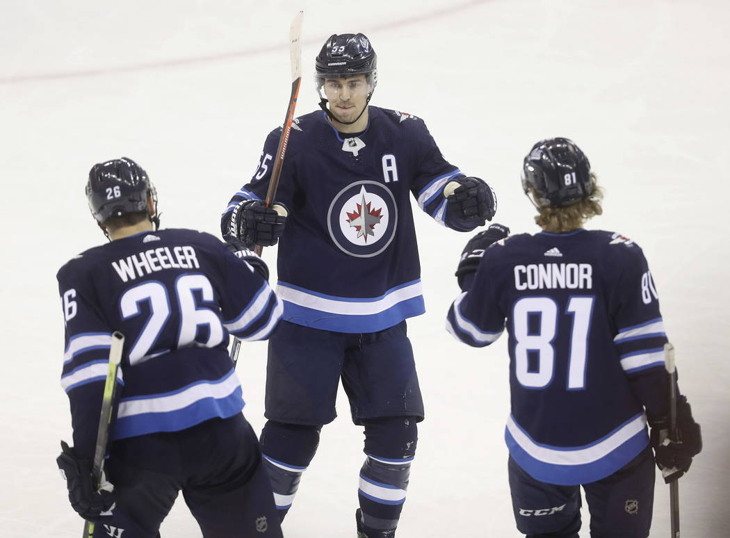 Winnipeg Jets' Blake Wheeler (26), Mark Scheifele (55) and Kyle Connor (81) celebrate after Connor scored an empty-net goal against the Vegas Golden Knights during the third period of an NHL hocke ...