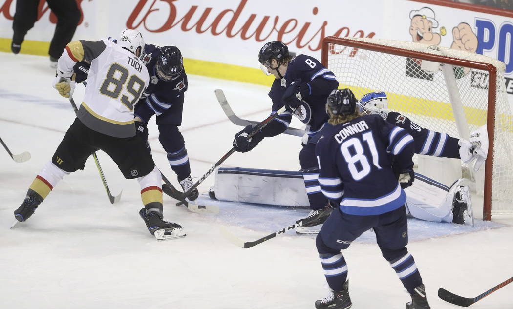 Winnipeg Jets' Josh Morrissey (44) and Jacob Trouba (8) defend Vegas Golden Knights' Alex Tuch (89) as goaltender Laurent Brossoit (30) gets his pad out to stop the puck during the third period of ...