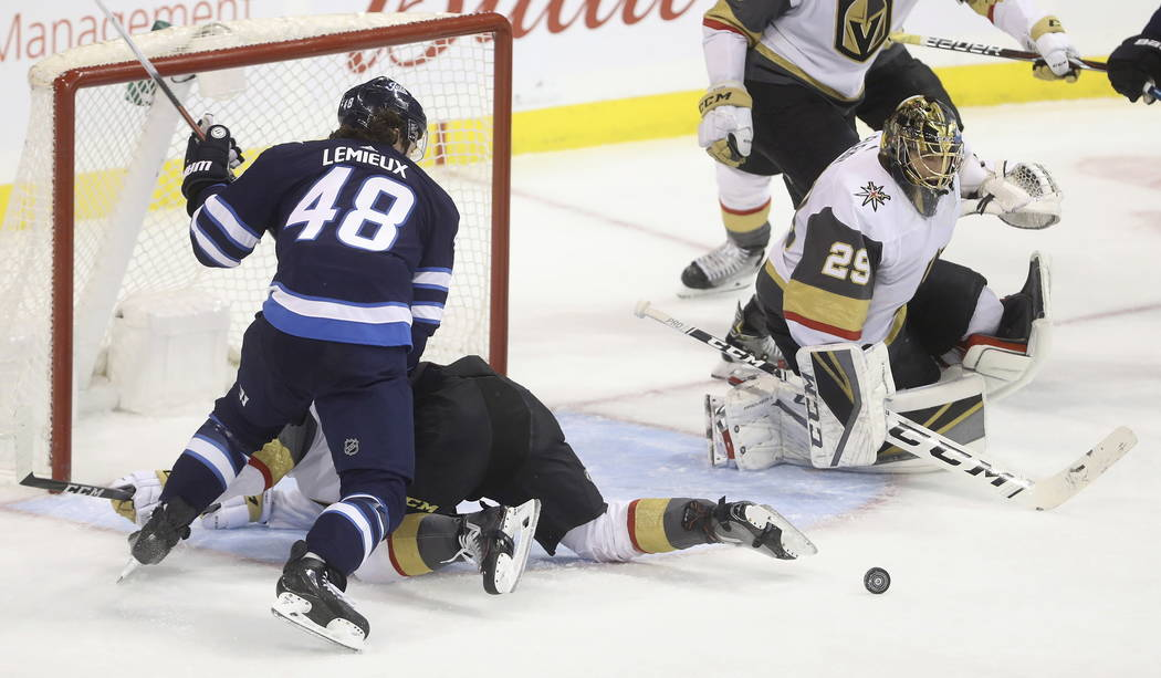 Winnipeg Jets' Brendan Lemieux (48) battles with Vegas Golden Knights' Nate Schmidt next to Golden Knights goaltender Marc-Andre Fleury (29) during the first period of an NHL hockey game Tuesday, ...