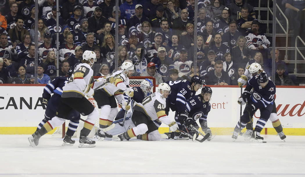 Winnipeg Jets and Vegas Golden Knights battle in front of Jets goaltender Laurent Brossoit (30) during the second period of an NHL hockey game Tuesday, Ja. 15, 2019, in Winnipeg, Manitoba. (Trevor ...