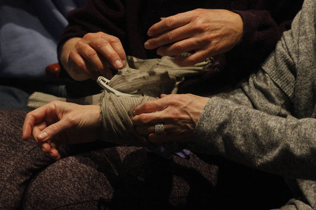 Members in the audience practice tying tourniquets around each other's arm during Stop the Bleed, a class teaching civilians how to control and stop life-threatening bleeds at the Summerlin Librar ...