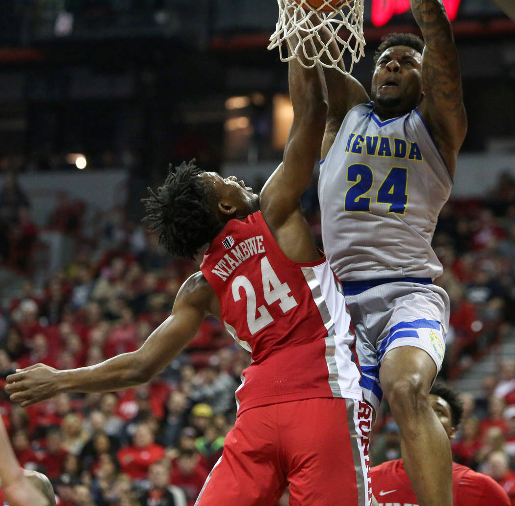 Nevada Wolf Pack forward Jordan Caroline (24) takes a shot while under pressure from UNLV Rebels forward Joel Ntambwe (24) during the first half of a basketball game at the Thomas & Mack Cente ...
