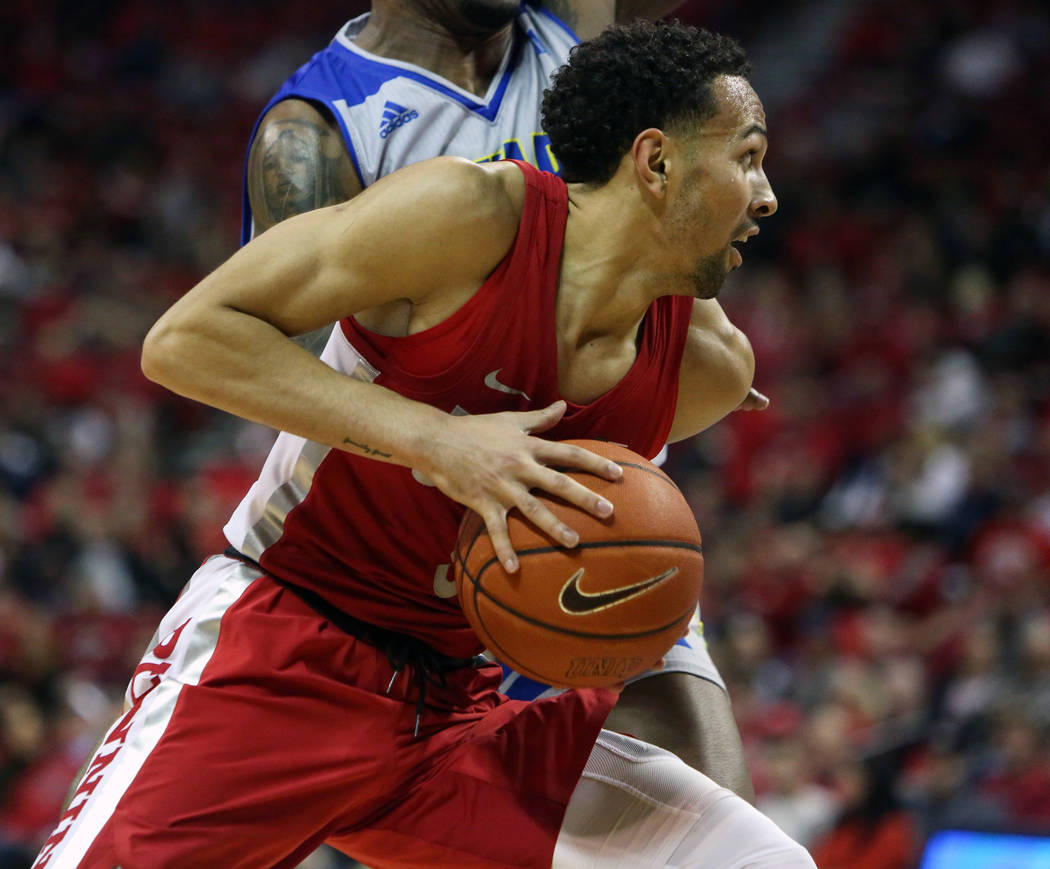 UNLV Rebels guard Noah Robotham (5) protects the ball while under pressure from Nevada Wolf Pack forward Jordan Caroline (24) during the second half of a basketball game at the Thomas & Mack C ...