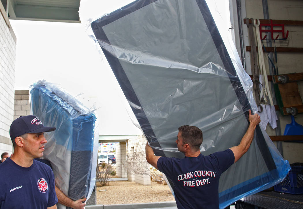 Firefighter Kevin Foreman, left, and Engineer Phil Robichaud unload mattresses at Fire Station 22 in Las Vegas, Wednesday, Jan. 16, 2019. Walker Furniture delivered new mattresses to all 30 Clark ...