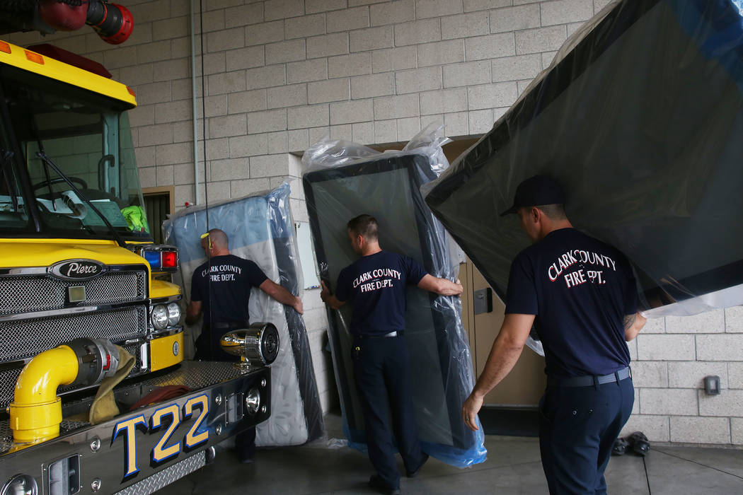 Workers carry mattresses to the dorms at Fire Station 22 in Las Vegas, Wednesday, Jan. 16, 2019. Walker Furniture delivered new mattresses to all 30 Clark County firehouses in the Las Vegas Valley ...