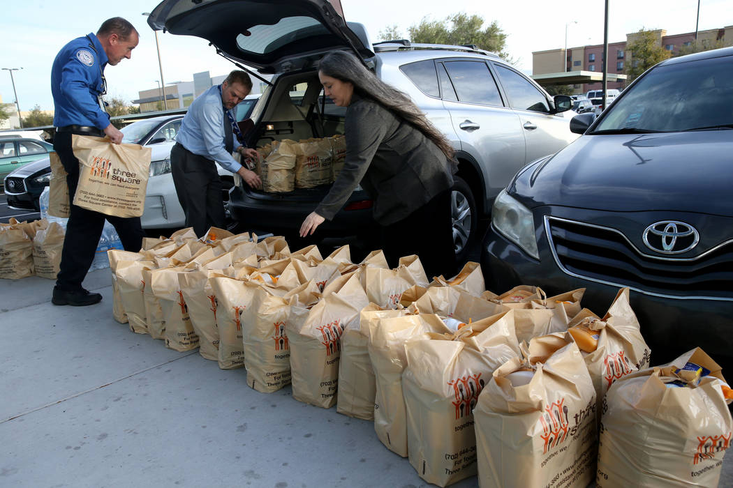 Transportation Security Administration employees load donated items to a car at TSA administrative offices in Las Vegas Wednesday, Jan. 16, 2019. Local food bank Three-Square supplied over 400 bag ...