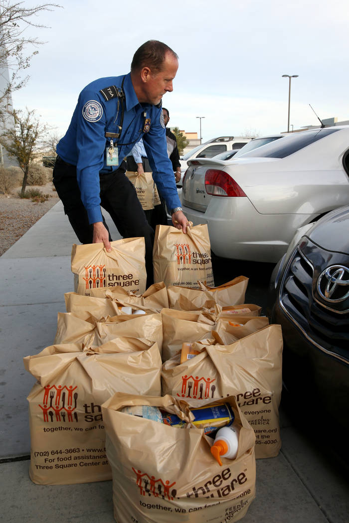 A Transportation Security Administration employees loads donated items to a car at TSA administrative offices in Las Vegas Wednesday, Jan. 16, 2019. Local food bank Three-Square supplied over 400 ...