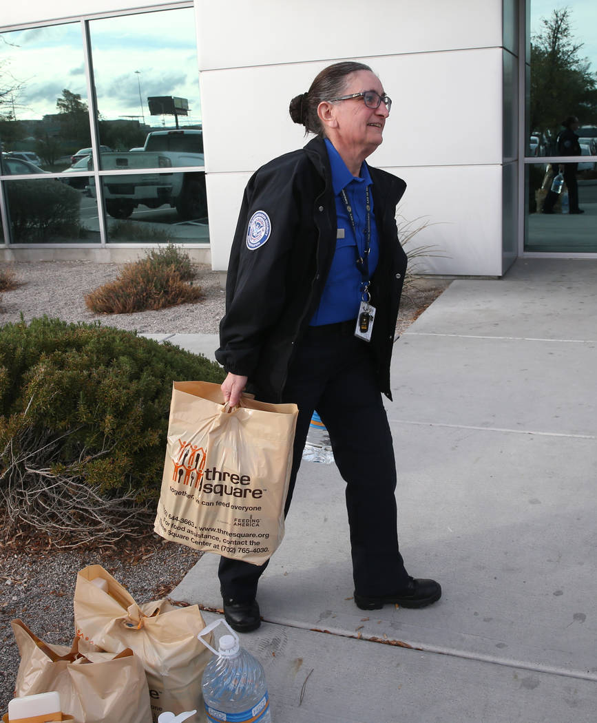 Transportation Security Administration officer Amy Jones loads donated items to her car at TSA administrative offices in Las Vegas Wednesday, Jan. 16, 2019. Local food bank Three-Square supplied o ...