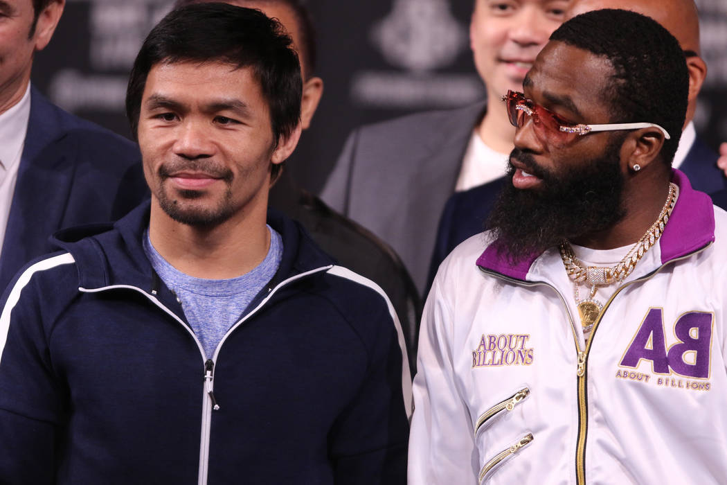 Boxer Adrien Broner, right, speaks to Manny Pacquiao after a news conference to promote their Jan. 19 welterweight title bout at the David Copperfield Theater at the MGM Grand in Las Vegas, Wednes ...