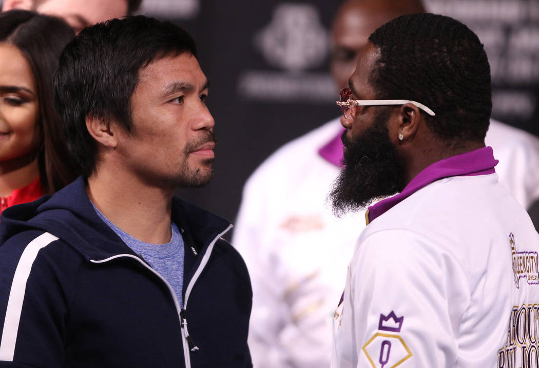Boxers Manny Pacquiao, left, and Adrien Broner stare each other down on Wednesday, Jan. 16, 2019 after a news conference at the David Copperfield Theater to promote their welterweight title bout t ...