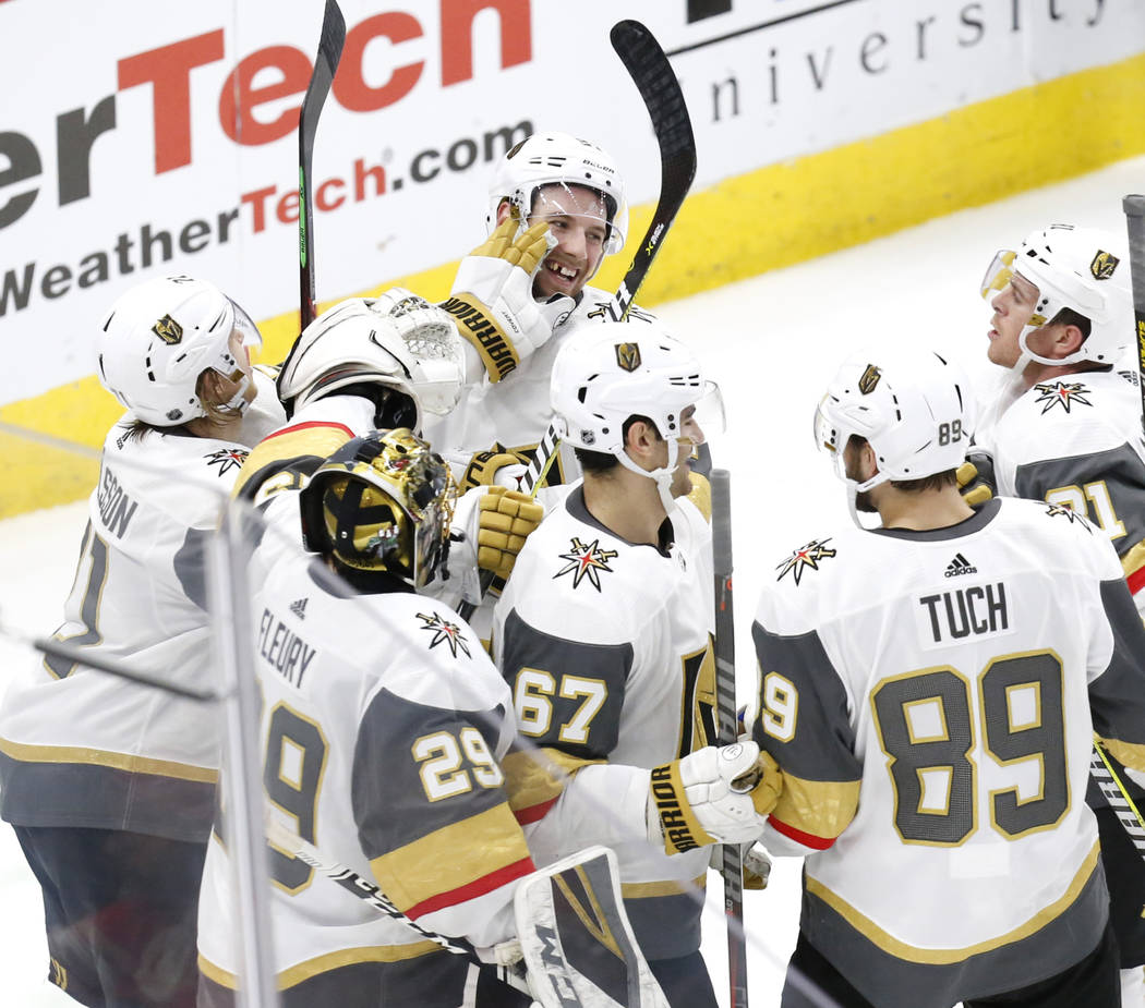 Vegas Golden Knights defenseman Shea Theodore,top center, celebrates with teammates after his goal against the Chicago Blackhawks during the overtime period of an NHL hockey game Saturday, Jan. 12 ...