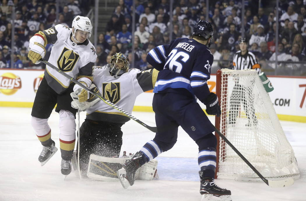 Winnipeg Jets' Blake Wheeler (26) and Vegas Golden Knights' Nick Holden (22) bump into Golden Knights goaltender Marc-Andre Fleury (29) during the second period of an NHL hockey game Tuesday, Ja. ...