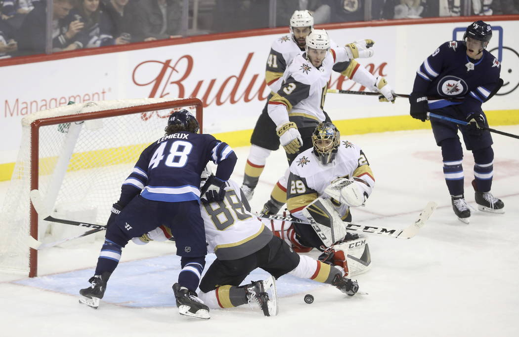 Winnipeg Jets' Brendan Lemieux (48) battles with Vegas Golden Knights' Nate Schmidt (88) in front of Golden Knights goaltender Marc-Andre Fleury (29) during the first period of an NHL hockey game ...