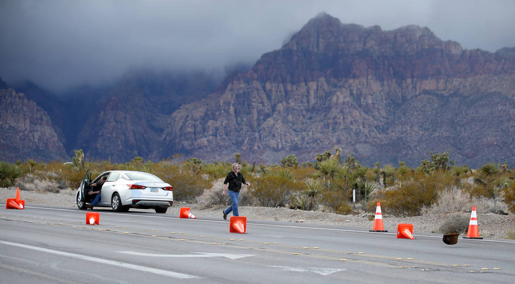 A person chases his hat that was blown off near the entrance to the closed Scenic Loop on Highway 159 in Red Rock Canyon National Conservation Area near Las Vegas Wednesday, Jan. 16, 2019. (K.M. C ...