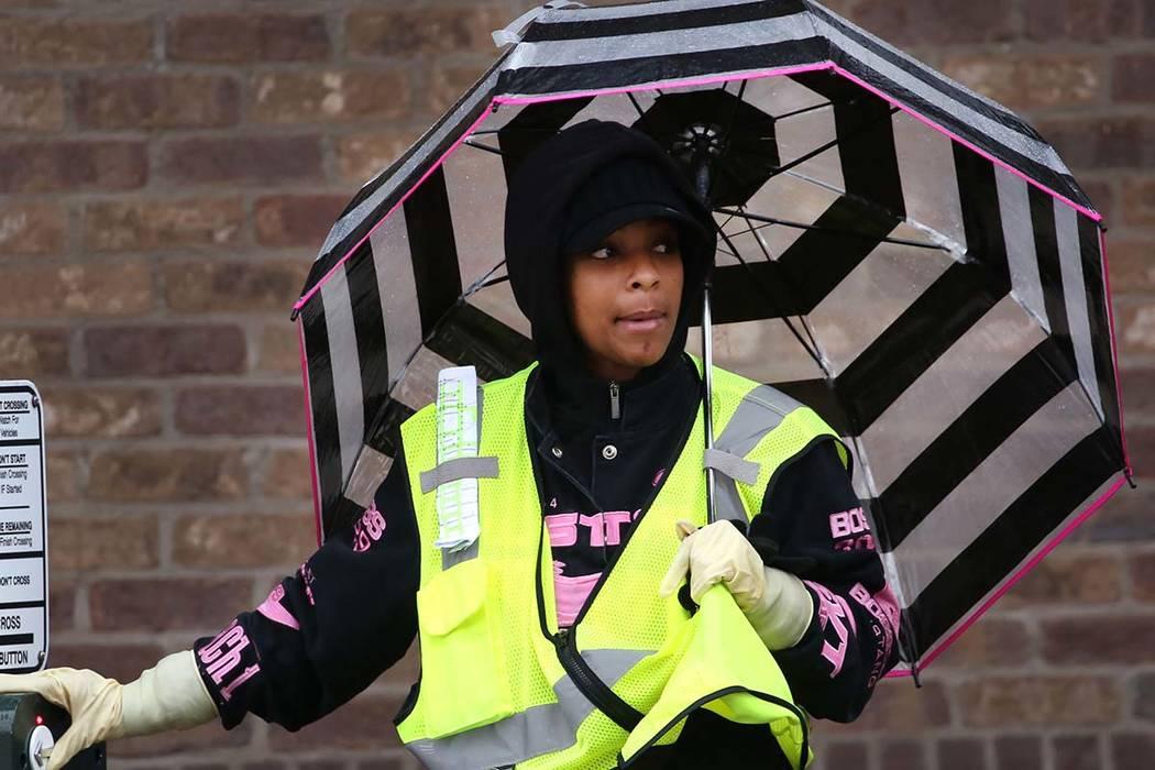 Carolyn Crawley holds an umbrella as she prepares to cross Stewart Avenue on Thursday, Jan. 17, 2019, in Las Vegas. (Bizuayehu Tesfaye/Las Vegas Review-Journal) @bizutesfaye