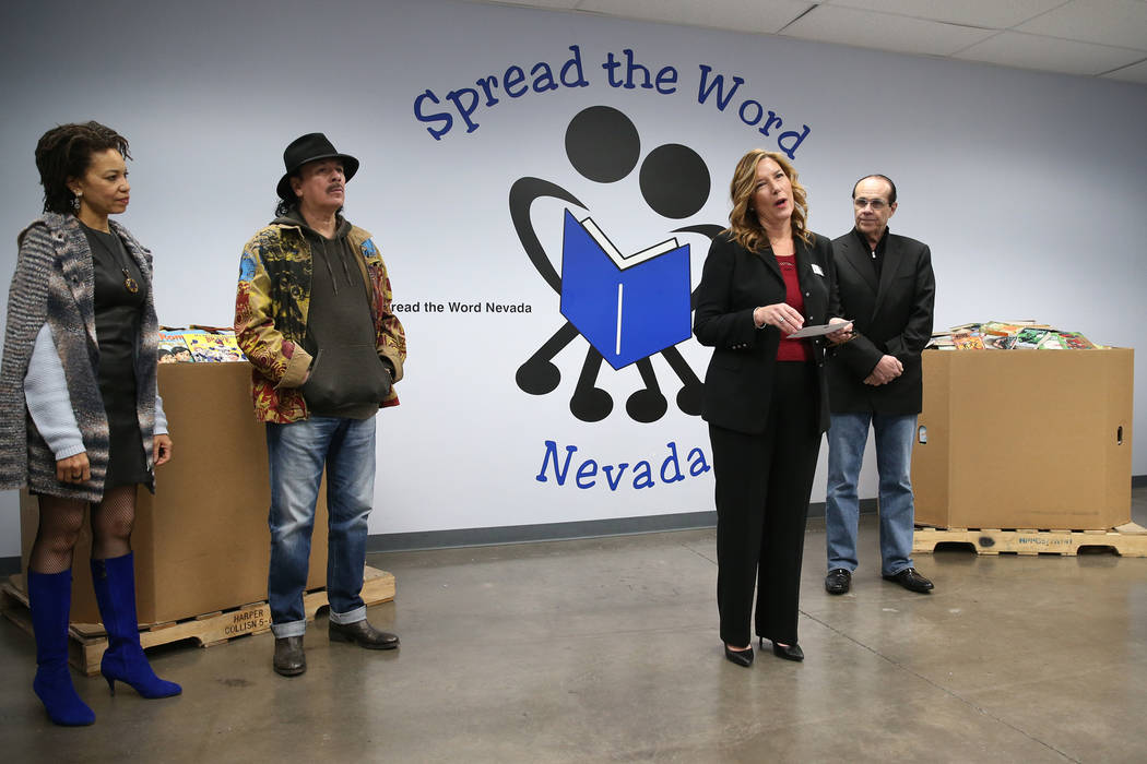 Lisa Habighorst, co-founder and executive director for Spread the Word Nevada, third from left, speaks during a an event with Carlos Santana, second from left, his wife Cindy Blackman Santana, far ...