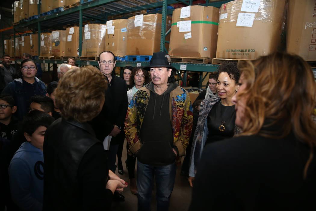Carlos Santana, center, with his wife Cindy Blackman Santana, right, tour the Spread the Word Nevada offices and warehouse in Henderson, Thursday, Jan. 17, 2019. Santana's Milagro Foundation made ...