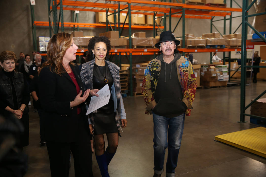 Carlos Santana, right, with his wife Cindy Blackman Santana, center, tour the Spread the Word Nevada offices with Lisa Habighorst, co-founder and executive director, in Henderson, Thursday, Jan. 1 ...