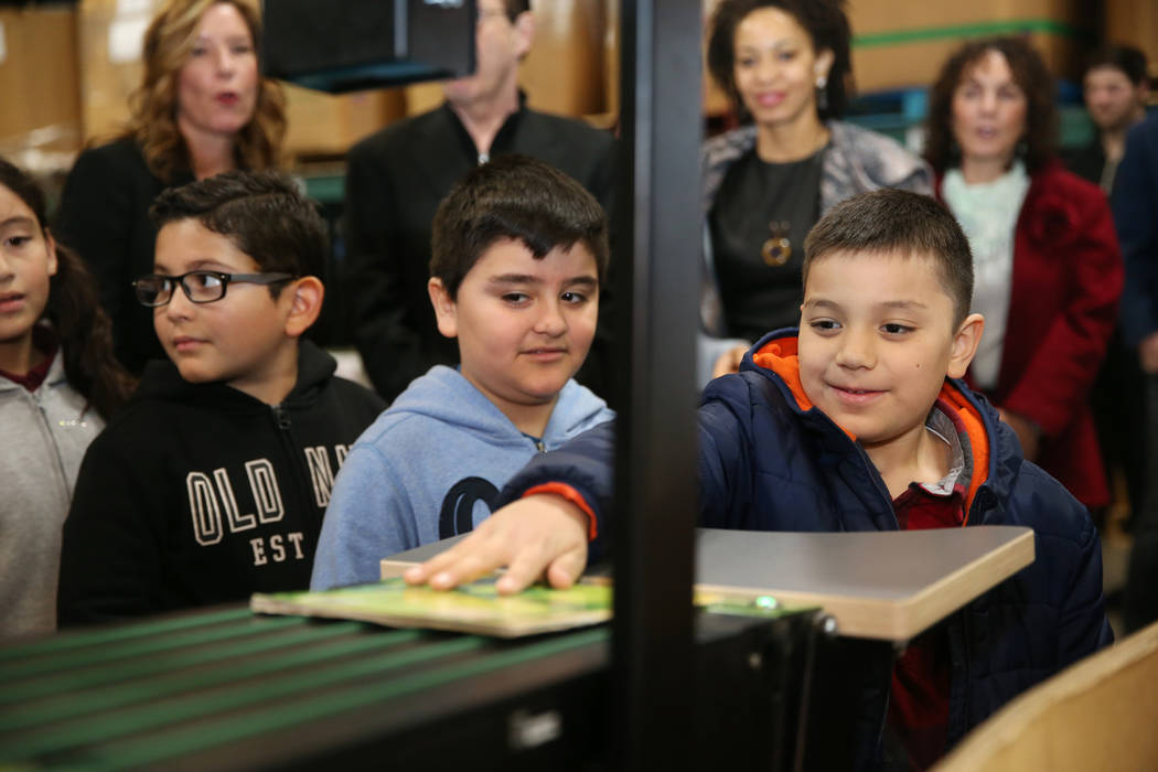 Peter Hernandez, right, 7, with Angel Lopez, 8, center, and Angel Martinez Pulido, 9, learn the process of automatic book assortment by grade level during a tour of the Spread the Word Nevada offi ...