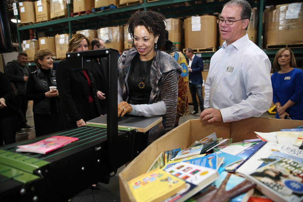 Cindy Blackman Santana, center, with David Ortlipp, right, director of operations at Spread the Word Nevada, learns the process of automatic book assortment by grade level during a tour of the Spr ...