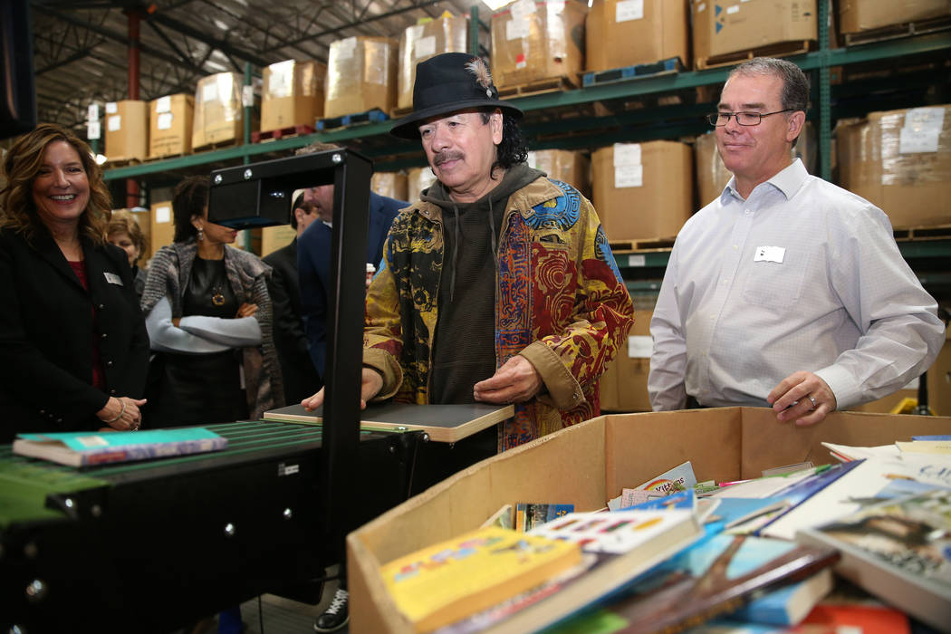 Carlos Santana, center, with David Ortlipp, right, director of operations at Spread the Word Nevada, learns the process of automatic book assortment by grade level during a tour of the Spread the ...