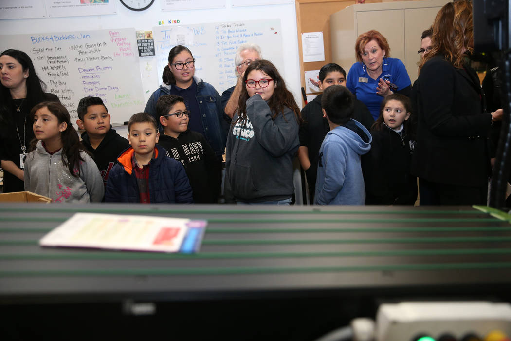 Students from Ronnow Elementary School tour the Spread the Word Nevada offices and warehouse in Henderson, Thursday, Jan. 17, 2019. Carlos Santana's Milagro Foundation made a donation to provide m ...
