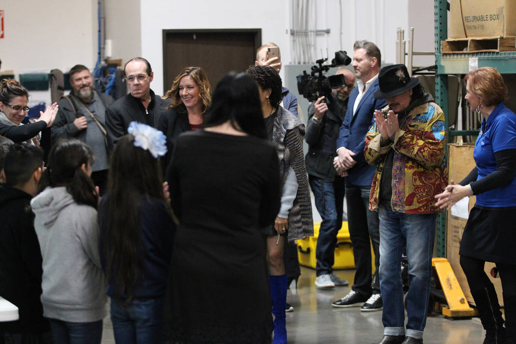 Carlos Santana, right, is welcomed to the Spread the Word Nevada offices and warehouse in Henderson, Thursday, Jan. 17, 2019. Santana's Milagro Foundation made a donation to provide more than 15,0 ...