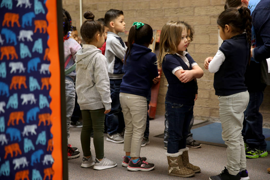 Prekindergarten students Mia Caamano Palafox, right, and Iris Vazquez prepare to walk to class with their teacher Leigh Todd at Tate Elementary in Las Vegas Thursday, Jan. 17, 2019. At left is Fer ...