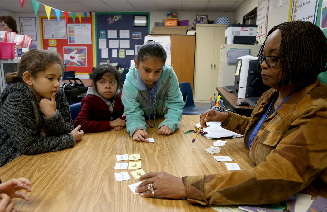 Jessie Jackson, a para professional tutor, teaches reading to second graders, from left, Aleina Luna, Jaqueline Cuevas Reyes and Melanie Campos Palma in the Zoom Reading Center at Tate Elementary ...