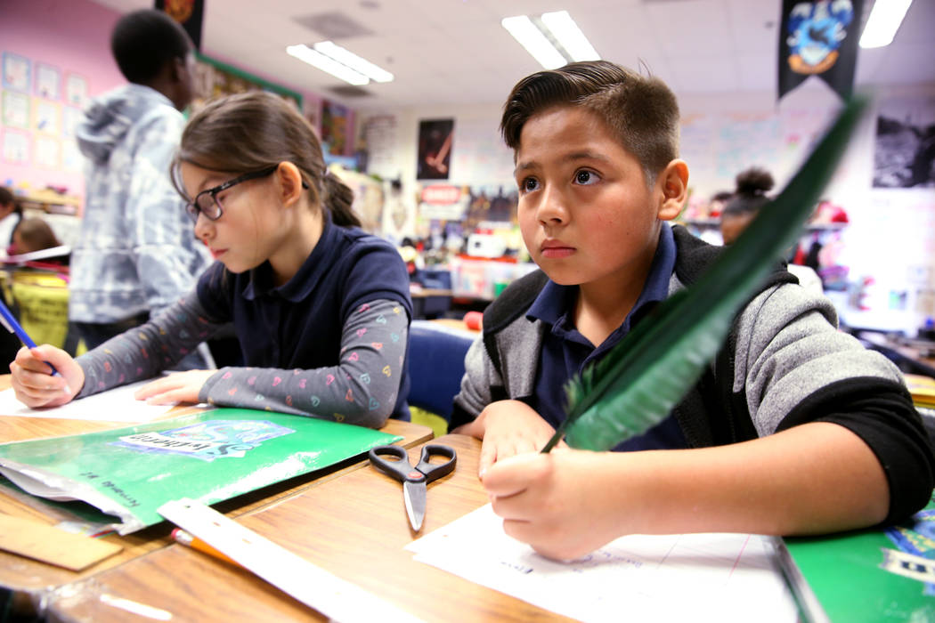 Arturo Vazquez Robledo uses a quill pen during a Harry Potter-themed reading lesson in Kathryn Faulkner's fourth grade class at Tate Elementary in Las Vegas Thursday, Jan. 17, 2019. At left is Fer ...