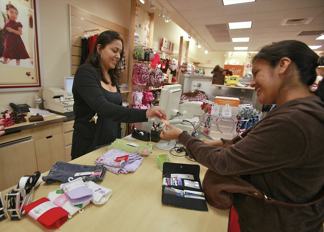 FILE - In this Monday, Oct. 4, 2010, file photo, Susi Ortiz, right, buys children's clothing at the Gymboree store at the Westside Pavilion Shopping Center in Los Angeles. Children's clothi ...