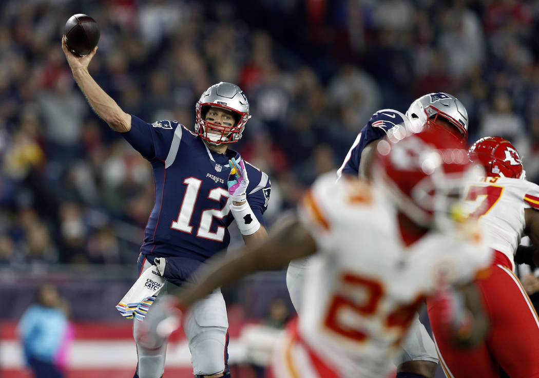 New England Patriots quarterback Tom Brady (12) passes under pressure from the Kansas City Chiefs during the first half of an NFL football game, Sunday, Oct. 14, 2018, in Foxborough, Mass. (AP Pho ...