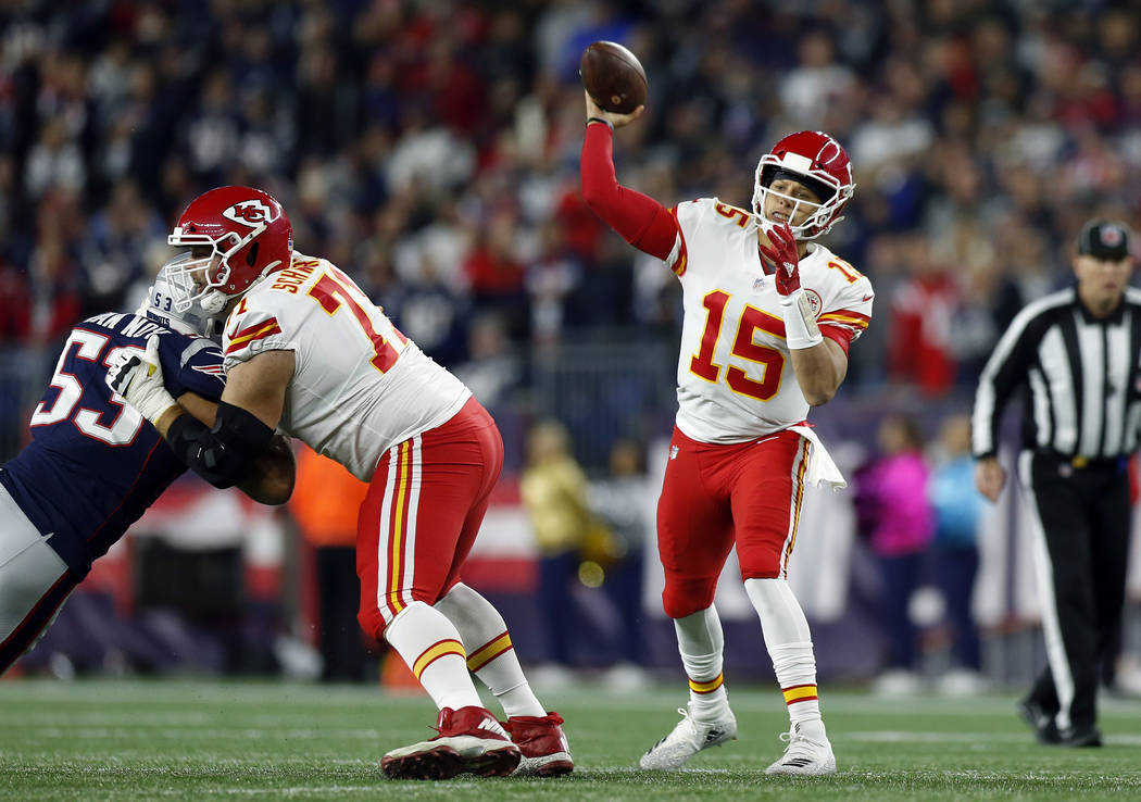 Kansas City Chiefs quarterback Patrick Mahomes (15) passes under pressure from New England Patriots linebacker Kyle Van Noy (53) during the first half of an NFL football game, Sunday, Oct. 14, 201 ...
