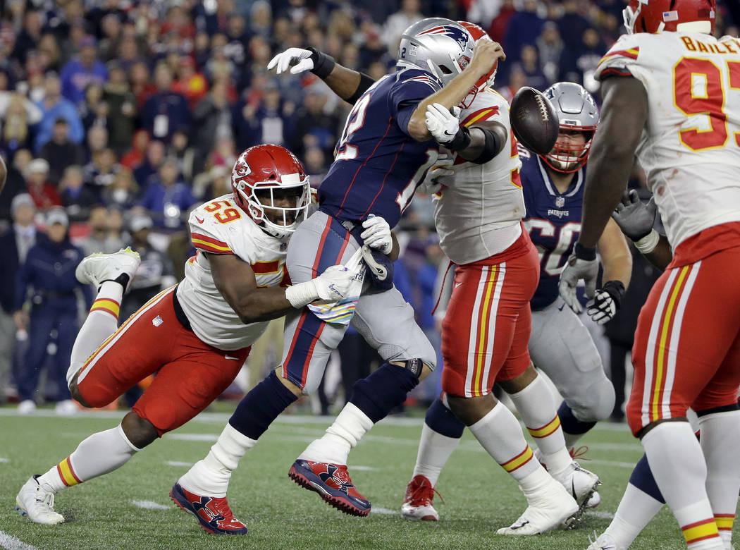 New England Patriots quarterback Tom Brady (12) fumbles the ball as Kansas City Chiefs linebacker Reggie Ragland (59) wraps him up during the second half of an NFL football game, Sunday, Oct. 14, ...