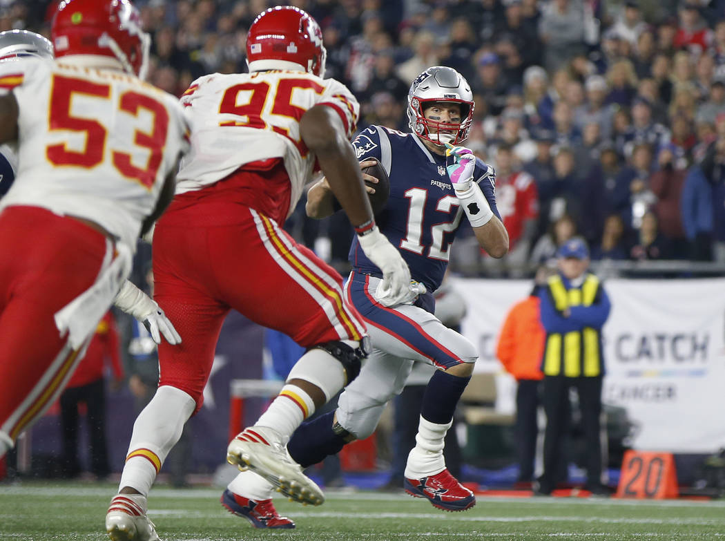 New England Patriots quarterback Tom Brady (12) runs past Kansas City Chiefs linebacker Anthony Hitchens (53) and defensive tackle Chris Jones (95) for a touchdown during the second half of an NFL ...